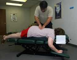 Chiropractor Joseph Medina does a Webster technique on the lower back of Traci Caldwell of Perry Township, who is pregnant.